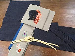縞結城袷着物と座布団の上の黒猫刺繍名古屋帯